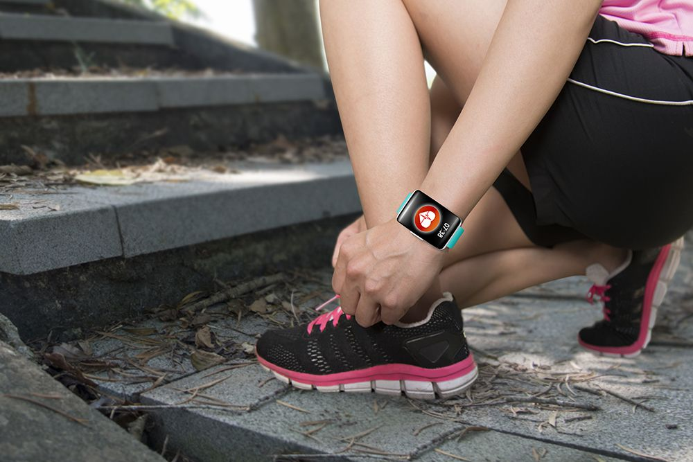 Woman tieing shoes with wearable tracking device on arm